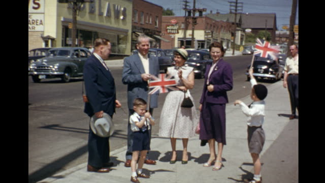 1953 home movie family standing outside appliance store waving union jacks on the day of queen elizabeth's coronation celebrations / toronto, canada - coronation stock videos and b-roll footage
