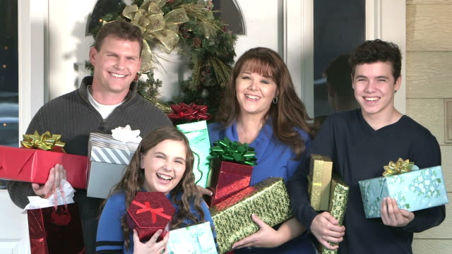 vídeos de stock e filmes b-roll de family standing outside front door with christmas gifts - 14 15 years