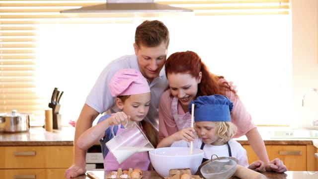 vidéos et rushes de family standing while cooking together - famille avec deux enfants