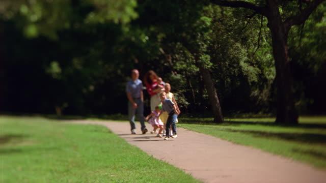 vidéos et rushes de a family strolling through a park - famille avec quatre enfants