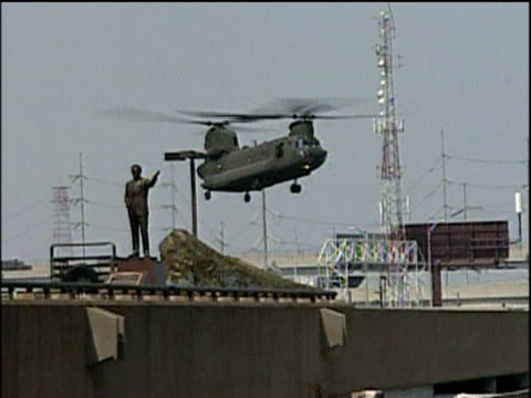 Family struggles towards US army helicopter waiting on freeway for evacuation Chinook lands to pick up more survivors as people riding horses and bicycle pass abandoned cars on freeway New Orleans following Hurricane Katrina; 4 Sep 05