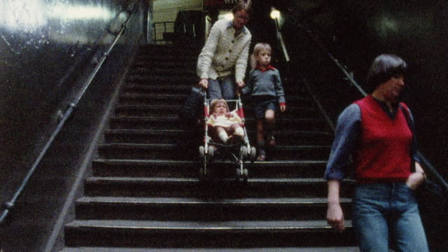 1978 MONTAGE Family struggling with stroller and disabled man on crutches have difficulty with long flights of stairs in the train stations / United Kingdom