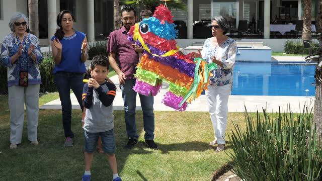 family supports young latino boy when punching piñata - papier stock videos & royalty-free footage