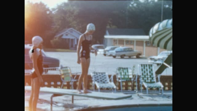 family swimming and having fun in motel pool / shot between 1962 and 1970 - sonnenschirm stock-videos und b-roll-filmmaterial