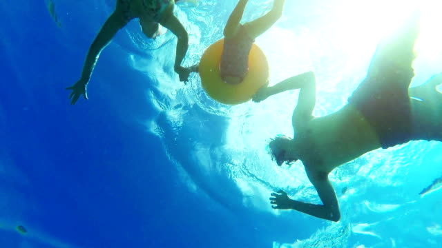 Family swimming and holding hands together with underwater view