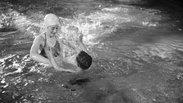 1948 ts family swimming together at the pioneer health centre in peckham / london, england - peckham health centre stock videos & royalty-free footage