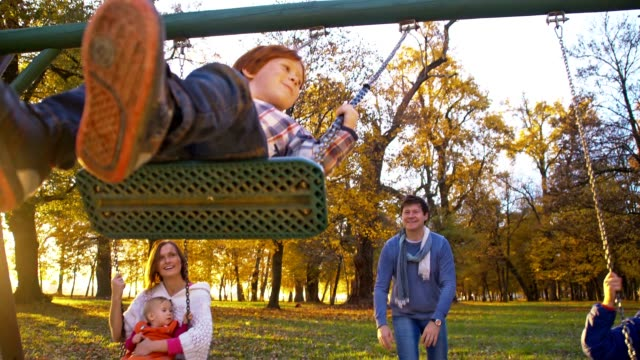 slo mo family swinging in the park - swinging stock videos & royalty-free footage
