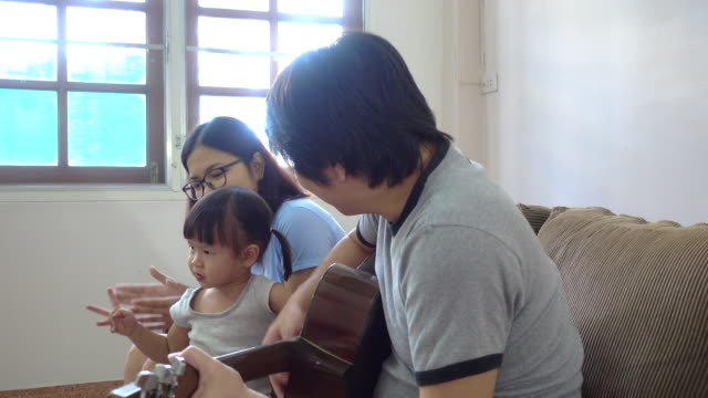 Family Tableau, Family singing together with father playing the guitar
