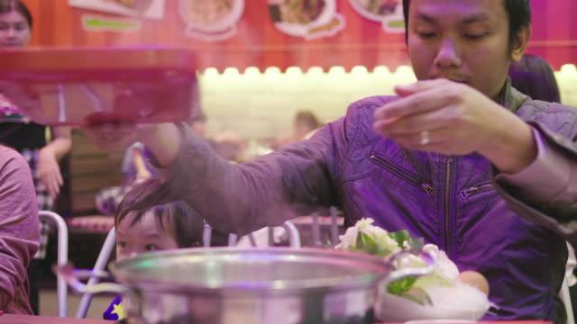family tableau of thai family are eating sukiyaki and thai food at the restaurant - sukiyaki stock videos and b-roll footage