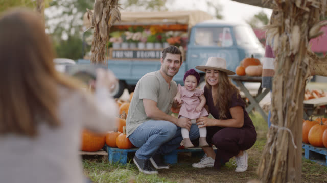family takes photos with their baby in a pumpkin batch at a farmers market - wilmington north carolina stock-videos und b-roll-filmmaterial
