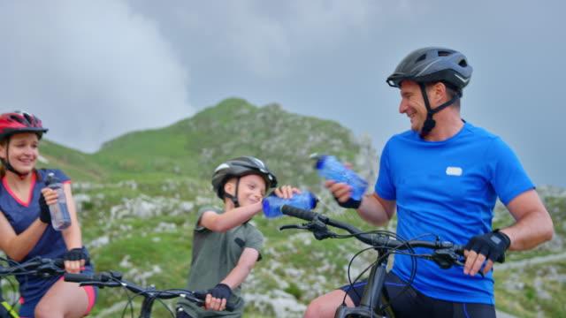vidéos et rushes de slo mo famille prenant une pause sur leurs vélos pour avoir un peu d'eau et le père et les enfants sont tromper et rire - faire du vélo tout terrain