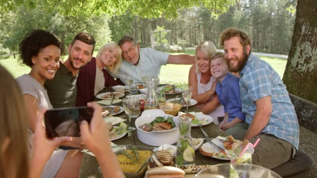 family taking a picture at the picnic table - large family stock videos and b-roll footage