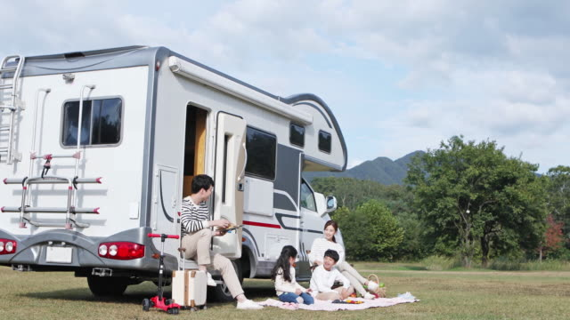 family taking a rest in front of camper trailer on the camping grounds - camper trailer stock videos and b-roll footage