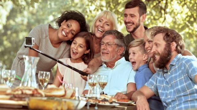 vídeos y material grabado en eventos de stock de slo mo familia teniendo un selfie en un picnic - reunión evento social