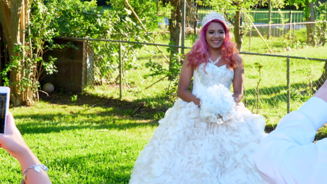 ms pan family taking photos with smartphones of young woman in quinceanera gown in backyard - 14 15 anni video stock e b–roll