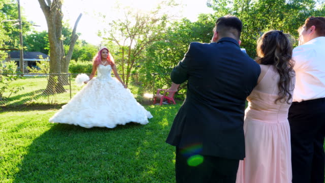 ms family taking photos with smartphones of young woman twirling in quinceanera gown in backyard - 14 15 anni video stock e b–roll