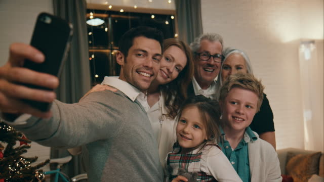 family taking pictures on christmas eve - photograph stock videos & royalty-free footage