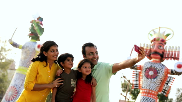 family taking self portrait picture in dussehra festival, delhi, india - dashahara stock-videos und b-roll-filmmaterial