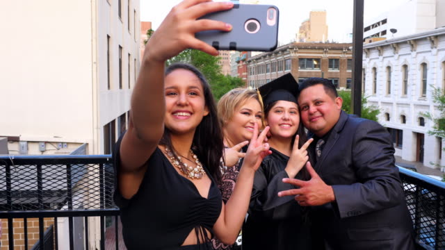 MS Family taking selfie with smartphone during graduation celebration on restaurant deck