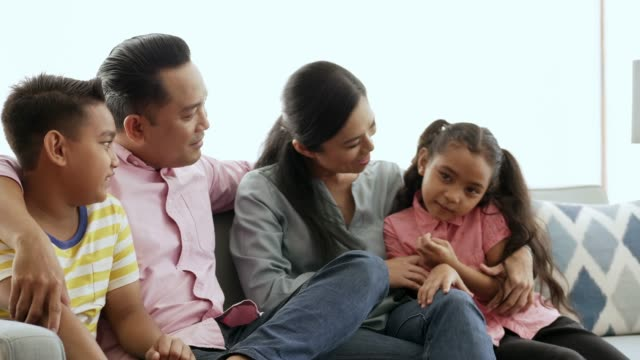 family talking while sitting on sofa at home - malay family stock videos and b-roll footage