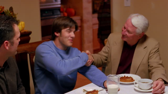 A family talks at the table, over pie, after Thanksgiving Dinner.