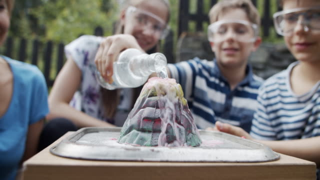 family testing volcano school project in back yard - school science project stock videos & royalty-free footage