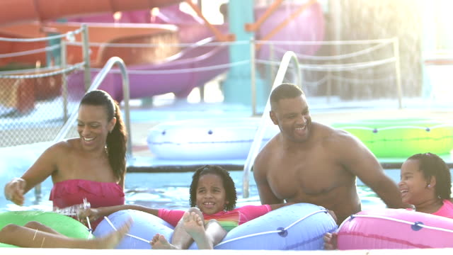 family, three children float on lazy river at water park - family with three children stock videos & royalty-free footage