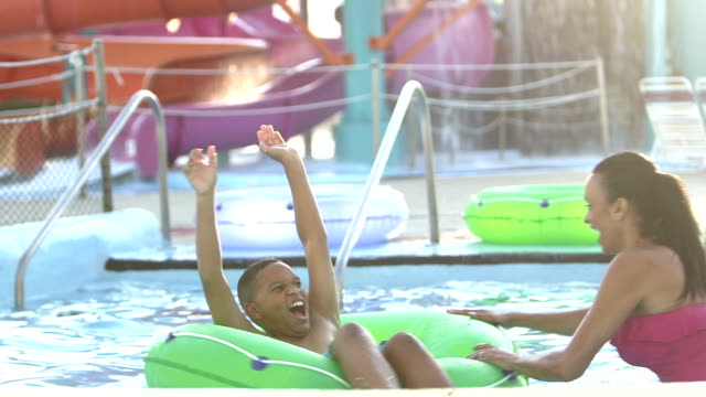 family, three children float on lazy river at water park - inflatable stock videos & royalty-free footage