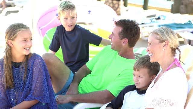 family, three children relaxing, talking on pool deck - family with three children stock videos & royalty-free footage