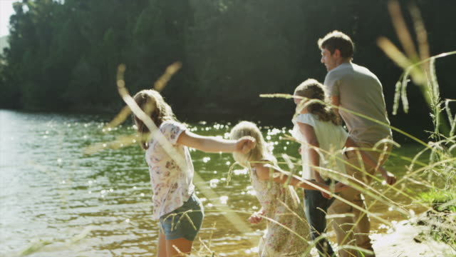 MS of family throwing stones into lake