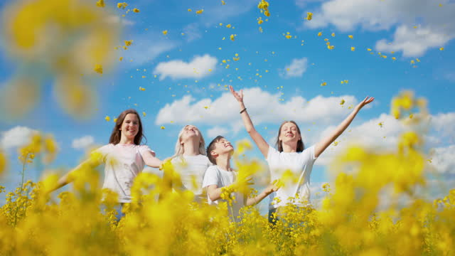 super slo mo family throwing yellow flowers in air - arms raised stock videos & royalty-free footage