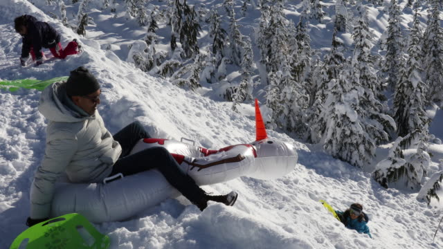 family toboggan down steep snow slope, towards trees - misfortune stock videos & royalty-free footage