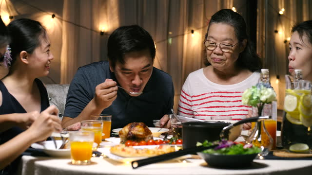 family together dinner in the evening of the celebration in the house. - dining table stock videos & royalty-free footage