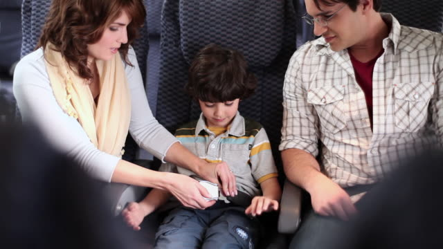family together on aeroplane - passenger cabin stock videos & royalty-free footage