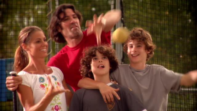 family tossing and dropping baseball in batting cage - gabbia di battuta video stock e b–roll