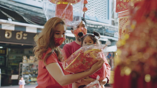 family travel chinese new year with face masks in the city. - chinese culture stock videos & royalty-free footage
