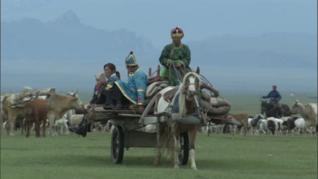Family travel on wagon loaded with collapsed ger, Bayanbulak grasslands.