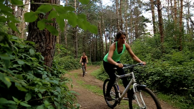 family trip on bikes in lush green nature,two sisters riding a bike - mountain bike stock videos & royalty-free footage
