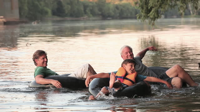 family tubing down a river - rubber ring stock videos & royalty-free footage