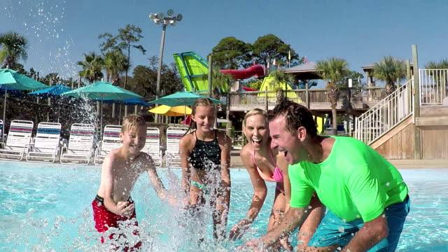 family, two children having fun at water park splashing - water slide stock videos & royalty-free footage