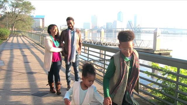Familia, dos niños caminando, hablando en el paseo marítimo de la ciudad