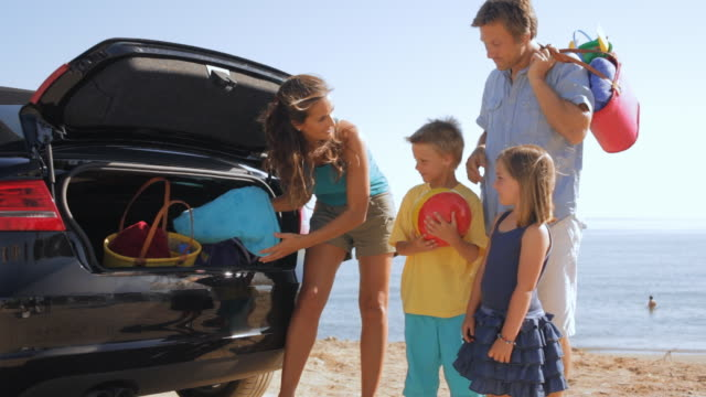 family unloading boot of car at beach - unpacking stock videos & royalty-free footage
