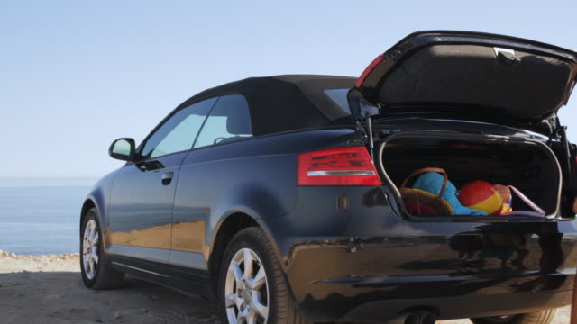 family unloading boot of car at beach - family convertible stock videos & royalty-free footage