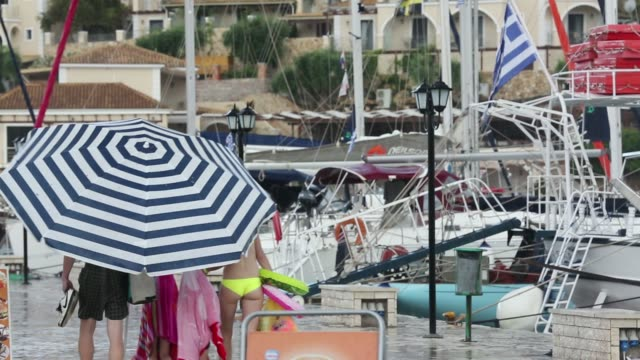 A family use a large beach umbrella to escape torrential rain and hail from a thunderstorm in Sivota, Greece.