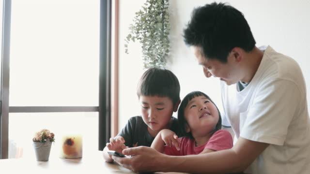 vídeos y material grabado en eventos de stock de familia usando un teléfono inteligente juntos en casa - niñez