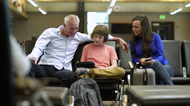 Family using a tablet while waiting at an airport