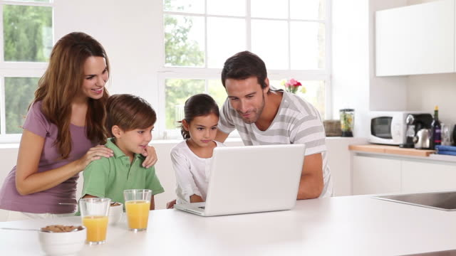 family using a white laptop in kitchen - using laptop stock videos & royalty-free footage