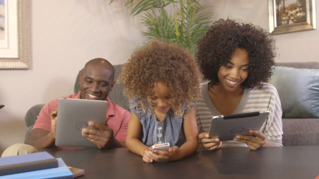 family using cellphone and tablets