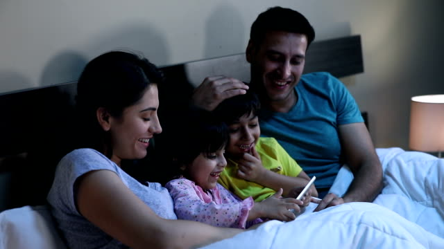 Family using digital tablet at home, Delhi, India