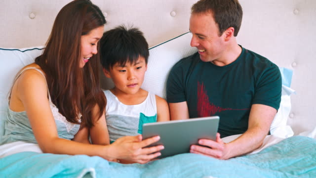 Family using digital tablet in the bed